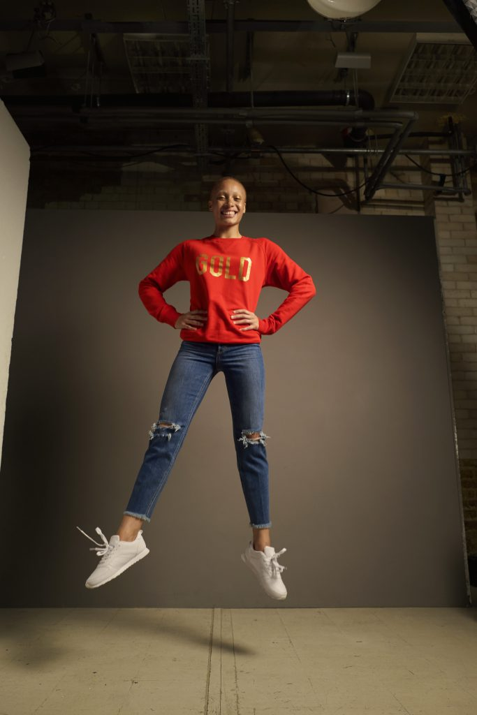 Adwoa Aboah in Selfish Mother GOLD sweatshirt for Save the Children.  £50 with 50% donation to Save the Children from thefmlystore.com  Join Adwoa in supporting Save the Children's Christmas Jumper Day on Friday 15th December - sign up at christmasjumperday.org
