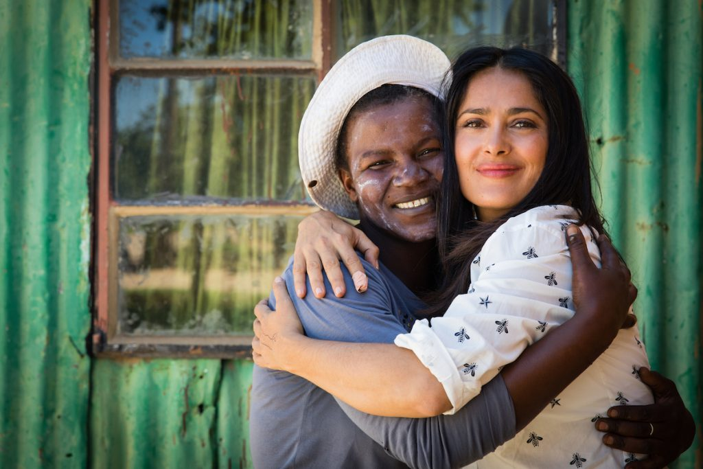 """Salma Hayek embraces Gabi Mokoena (41), an HIV-positive mother benefitting from mothers2mothers work in Phola Township, Mpumalanga Province, South Africa. Through mothers2mothers (m2m), Gabi formed a trusted relationship with a m2m Mentor Mother, who provided her with lifesaving education and support to ensure that her daughter was born HIV-negative and remains that way as she grows up.    m2m trains, employs and empowers local HIV-positive mothers as Mentor Mothers, frontline healthcare workers based in understaffed health clinics and communities. Mentor Mothers' intimate understanding of the social and cultural challenges of living with HIV gives them a unique ability to form trusted relationships with other women and their families, vital to helping them overcome their fears and make lifesaving decisions. Mentor Mothers are professionalised, employed and economically empowered, fighting stigma and discrimination by example.    About mothers2mothers    mothers2mothers (m2m) is an international NGO founded in Cape Town, South Africa in 2001. m2m employs and trains HIV-positive women as """"Mentor Mothers"""" to deliver health services, advice, and support to women and their families at health facilities and in local communities. From an initial focus on eliminating mother-to-child transmission of HIV, m2m has expanded into five related areas to deliver benefits for women and their families at all stages of life. As well as a continued focus on HIV-prevention and education, m2m's services now also include early childhood development, paediatric care and support, and adolescent mentoring.      In 2016 alone, m2m and its partners enrolled almost two million new clients into care across seven African countries. Results show that m2m has virtually eliminated mother-to-child transmission of HIV amongst its clients, and is making significant strides in expanding the scope and scale of its other services.      For more, visit: www.m2m.org."""