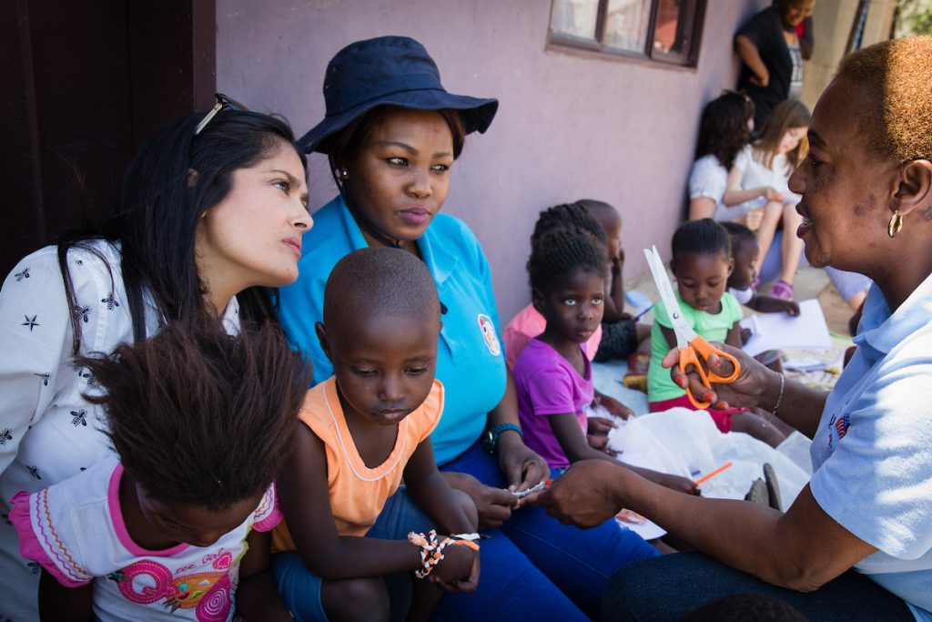 "Salma Hayek visiting the mothers2mothers (m2m) Early Childhood Household Stimulation Project in Phola Township, Mpumalanga, South Africa. Salma is sitting next to m2m Mentor Mother Mpumi Ndala (28) and talking to Mentor Mother Sylvia Mdluli (45) about their work to improve children's cognitive, social-emotional, physical and language developments and eliminate mother-to-child transmission of HIV. The ECHS Project was designed by mothers2mothers (m2m) to ensure children thrive, rather than just survive. Delivered by m2m's Mentor Mothers—HIV-positive women who work as frontline healthcare workers in local clinics and door-to-door in communities—the ECHS project empowers caregivers to create the safe, high-quality environment required to underpin successful early childhood development for their children (0-5 years old). Playgroups and one-to-one education and training is delivered at household level and at local venues such as community creches. About mothers2mothers mothers2mothers (m2m) is an international NGO founded in Cape Town, South Africa in 2001. m2m employs and trains HIV-positive women as ""Mentor Mothers"" to deliver health services, advice, and support to women and their families at health facilities and in local communities. From an initial focus on eliminating mother-to-child transmission of HIV, m2m has expanded into five related areas to deliver benefits for women and their families at all stages of life. As well as a continued focus on HIV-prevention and education, m2m's services now also include early childhood development, paediatric care and support, and adolescent mentoring. In 2016 alone, m2m and its partners enrolled almost two million new clients into care across seven African countries. Results show that m2m has virtually eliminated mother-to-child transmission of HIV amongst its clients, and is making significant strides in expanding the scope and scale of its other services. For more, visit: www.m2m.org."
